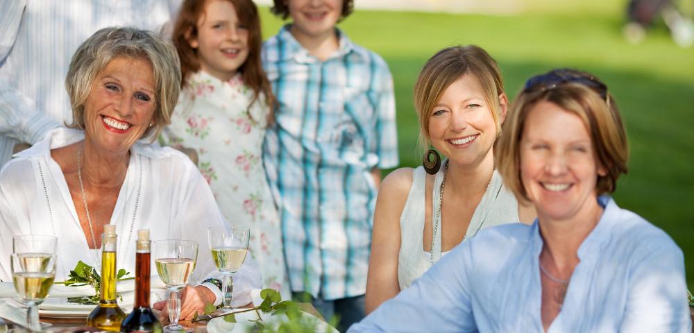 Happy family having dinner in the garden in summer