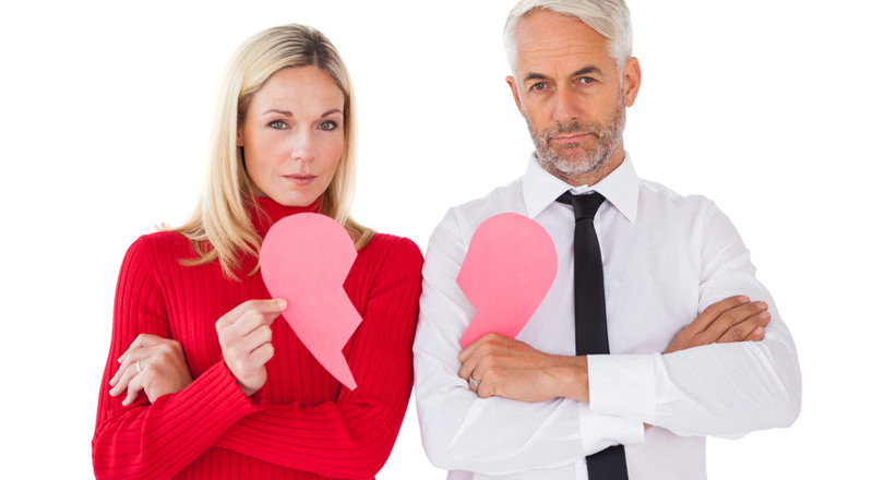 Couple not talking holding two halves of broken heart on white background